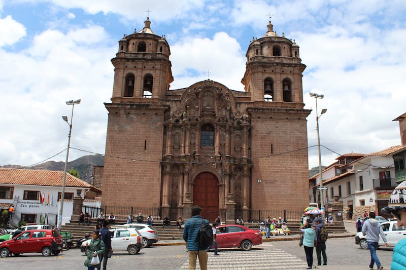 person looking at church in center of cusco